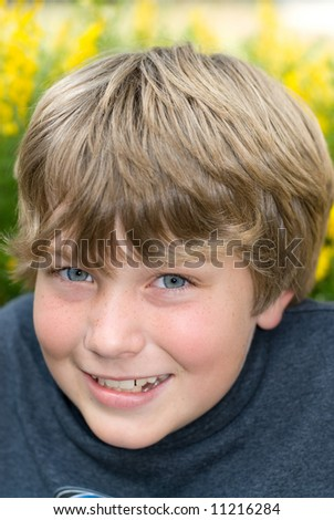 A 9 year old boy smiles while resting in a field of yellow springtime flowers - stock photo