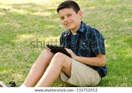 A 10 year old boy smiling while he sits with a tablet  at the park. - stock photo