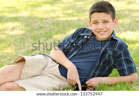 A 10 year old boy smiling while he touches his tablet with his finger. - stock photo