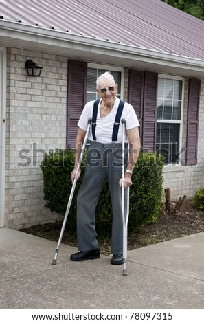 A 93 year old elderly man with crutches, standing alone outside his apartment with a big smile on his face - stock photo