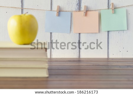 A  yellow apple with three sheets of paper hanging on clothespins. Robin egg blue background and three books. Vintage look. - stock photo