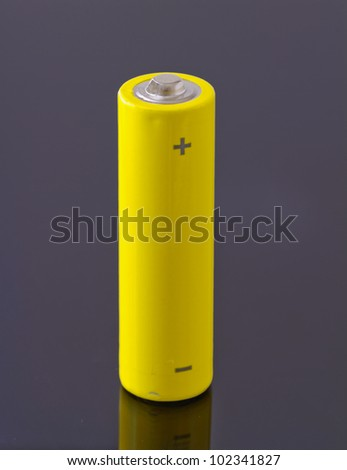 A yellow battery over a black reflecting background - stock photo