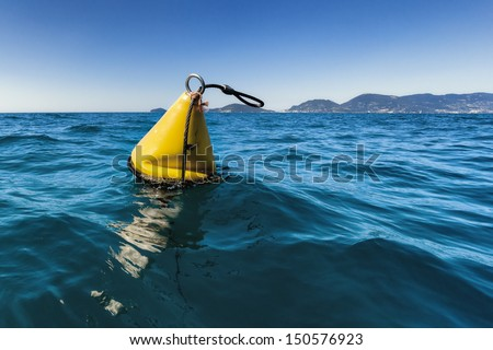 A yellow buoy in the sea - stock photo