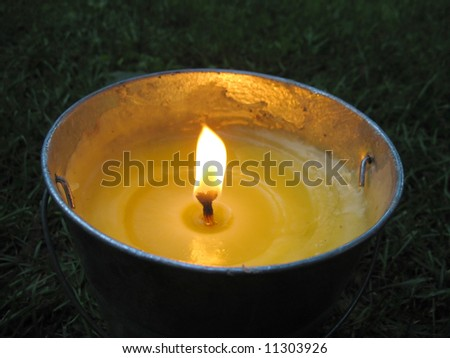 A yellow citronella bucket candle - perfect for those summertime evenings to keep the mosquitos away. - stock photo