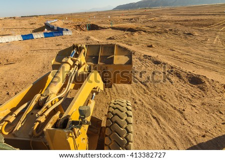 A yellow Construction Loader working at a construction site - stock photo
