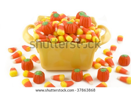 A yellow dish filled with Halloween candy corn and candy pumpkins, isolated on white background with copy space - stock photo