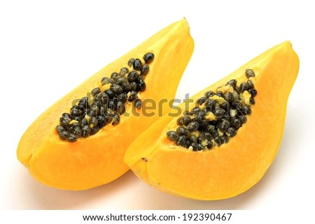 A yellow fruit with small black seeds in it. - stock photo