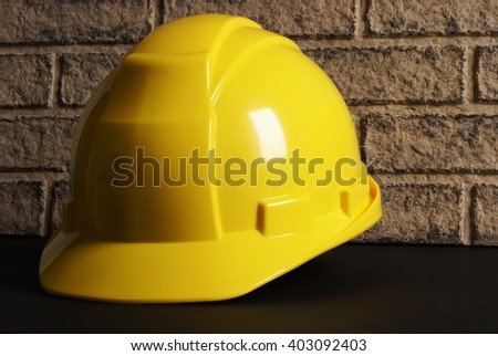 A yellow hardhat rests on a construction site. - stock photo