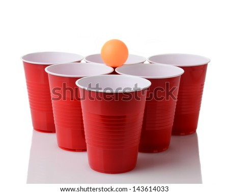 A yellow ping pong ball resting on a group of red plastic cups arranged for playing Beer Pong isolated on a white background with reflection. - stock photo