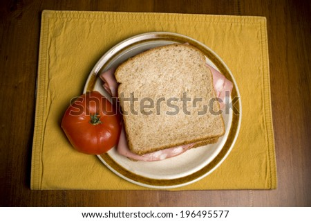 A yellow placemat holding a plate with a bologna sandwich and an apple. - stock photo