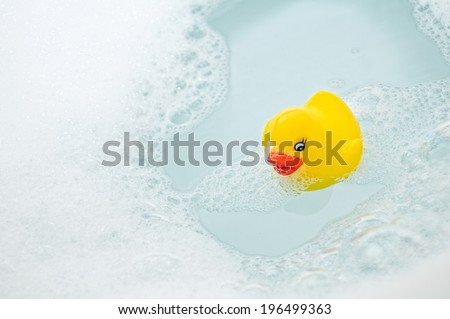 A yellow rubber duck sitting in soapy water. - stock photo