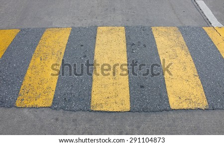 A yellow speed bump for slowing traffic - stock photo