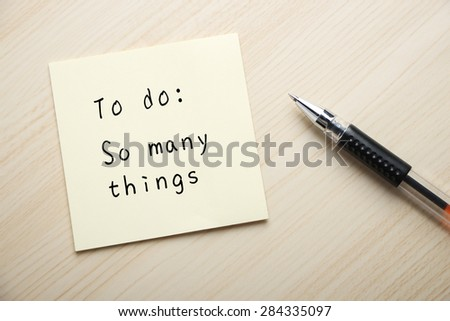 A yellow sticky note is written something on the desk with a ball pen aside. - stock photo
