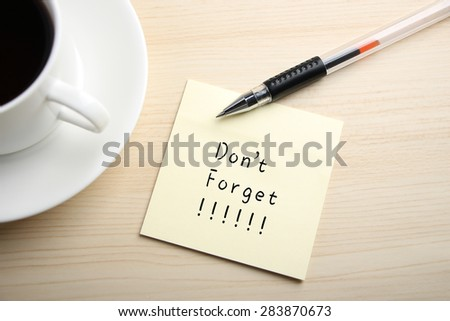 A yellow sticky note is written something on the desk with a cup of coffee and a ball pen aside. - stock photo