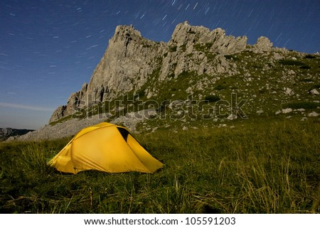 A yellow tent illuminated in mountains, in the middle of the night - stock photo