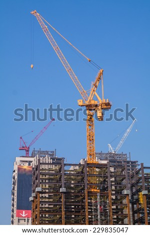 A Yellow Tower Crane on Top of A Steel Skeleton Frame. With Two More Cranes and Blue Sky in The Background. - stock photo