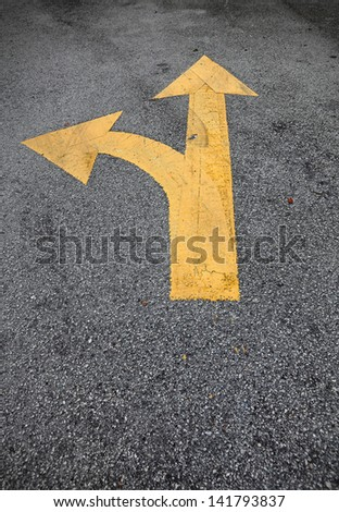 A yellow traffic arrow signage on an asphalt road indicating a detour left turn. - stock photo