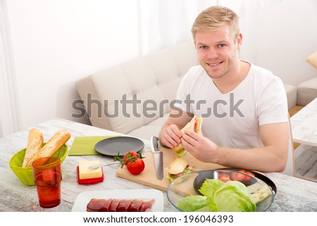 A young adult man eating a sandwich at home. - stock photo