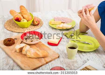 A young adult woman eating an european style ham sandwich.