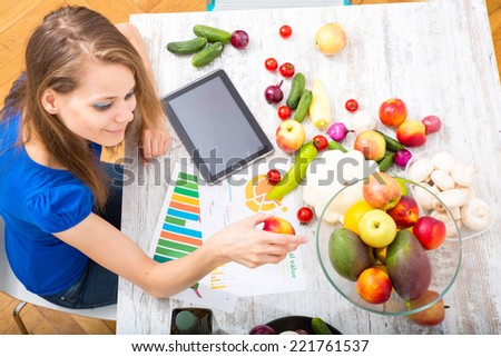 A young adult woman informing herself with a tablet PC about nutritional values of fruits and vegetables. - stock photo