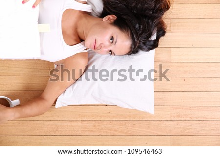 A young adult woman relaxing after reading a book. - stock photo