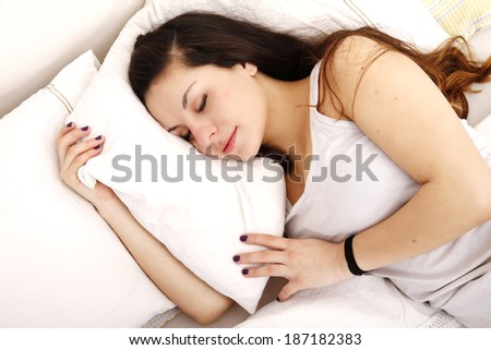 A young adult Woman sleeping on the Bed. - stock photo