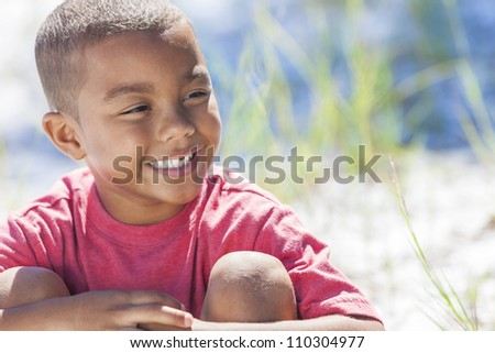 A young African American boy child outside in the summer sunshine - stock photo
