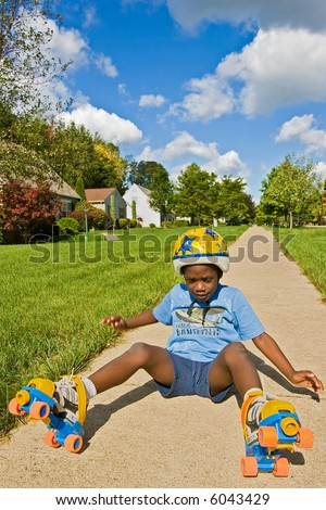 A young African American boy falls down while roller skating - wearing skates and a helmet. - stock photo