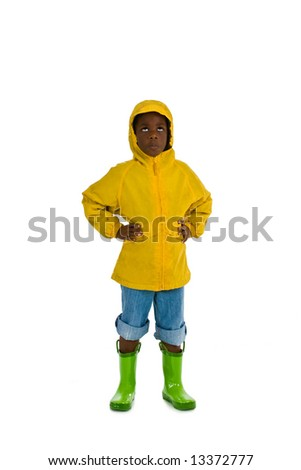 A young African American boy wearing a yellow rain slicker. Isolated on a white background. - stock photo