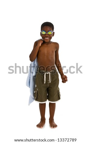 A young African American boy wearing swim trunks and goggles, and carrying a towel. Isolated on a white background. - stock photo