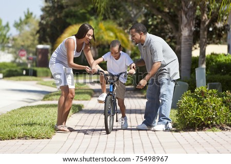 A young African American family with boy child riding his bicycle and his happy excited parents encouraging him. - stock photo