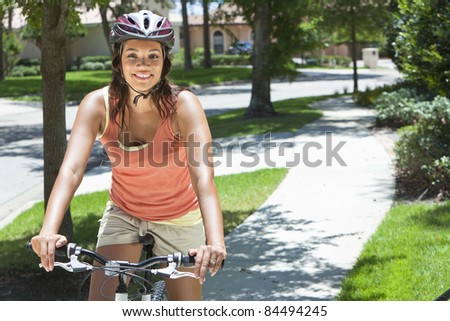 A young African American woman riding bicycle in the summer - stock photo