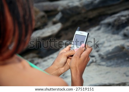 a young african american woman text messages on her cell phone at the beach - stock photo