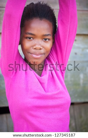 A young African girl with her hands in the air. - stock photo