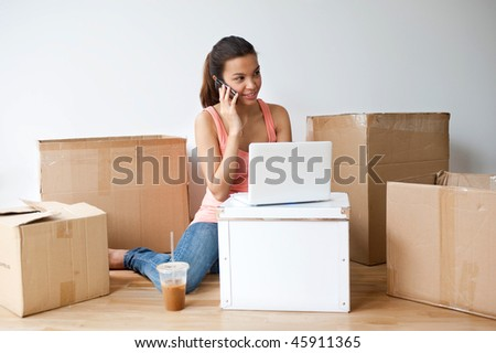 A young and attractive asian woman talking on the phone and using her laptop in her new home - stock photo