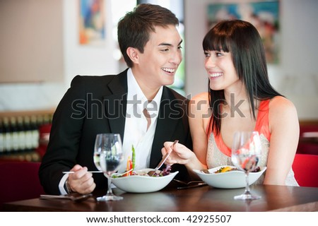 A young and attractive couple dining in a restaurant - stock photo