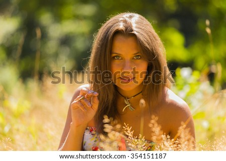 A young and attractive girl in beautiful summer dress middle of sunny meadows. Cheerful girl basking in the warm rays of the summer sun. Beautiful image of a carefree girl.   - stock photo
