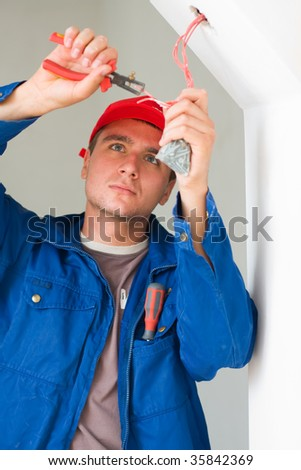 A young and confident electrician installing lights in a new house - part of a series. - stock photo