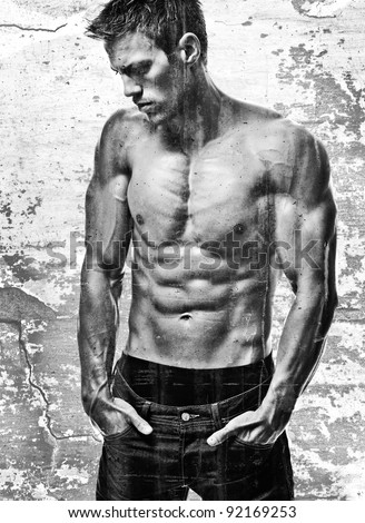 a young and fit male model posing his muscles in a grunge setting - stock photo