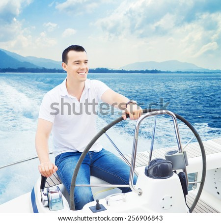 A young and handsome Caucasian man sailing in the sea on a boat on a sunny day. - stock photo