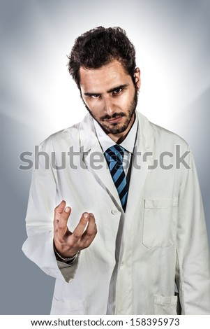 a young and handsome megalomaniac doctor or medical student - stock photo