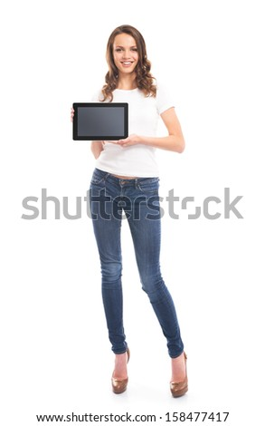 A young and happy girl in stylish jeans holding a tablet computer isolated on a white background. - stock photo