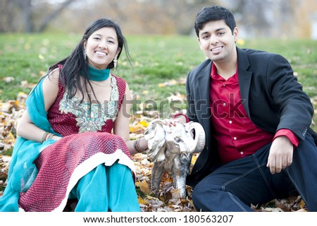 A young and happy Indian couple posing with a metal elephant in the park on a cloudy day. - stock photo