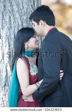 A young and happy Indian man kissing his bride on the forehead on a cloudy day in the Fall. - stock photo