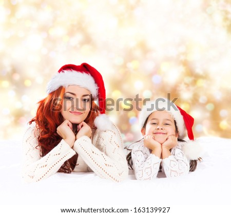 A young and happy mother and daughter over the Christmas background - stock photo