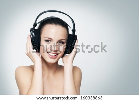 A young and pretty teenage girl listening to the music in headphones - stock photo