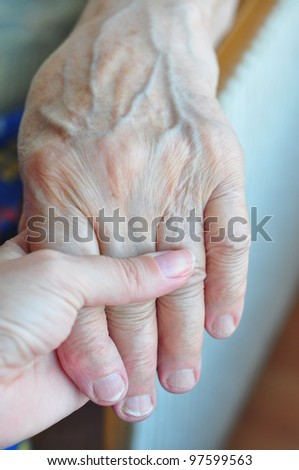 a young and senior hands holding each other - stock photo
