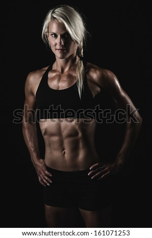 a young and very fit woman flexing her muscles - stock photo