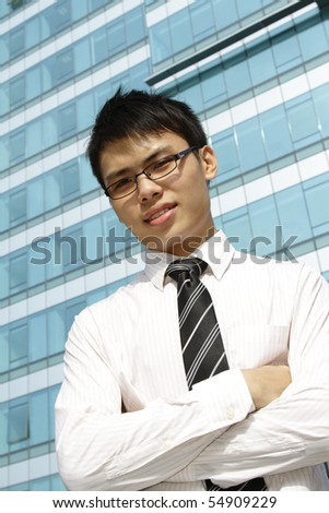 A young Asian business executive standing in front of an office building - stock photo