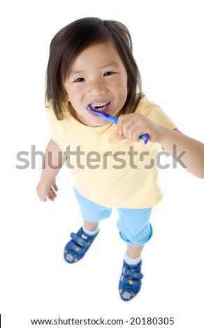 A young asian girl brushing her teeth. - stock photo